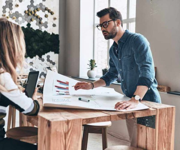 Discussing strategy. Two young modern business people in smart casual wear using blueprint while working in the creative working space